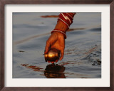 Woman Praying on the Banks of the River Ganges Fills Water into a Copper Vessel for a Ritual Framed Photographic Print