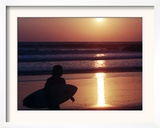 A Surfer is Silhouetted by the Setting Sun as He Leaves the Pacific Ocean on Venice Beach Framed Photographic Print