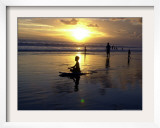 An Indonesian Boy Sits on His Surfboard at Sunset Framed Photographic Print