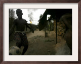 Two Local Children Play Soccer Near Their House While a Gas Flare Burns Framed Photographic Print