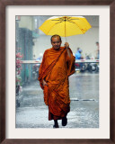 A Buddhist Monk Walks in the Rain on a Street in Bangkok Framed Photographic Print