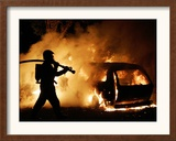 A Firefighter Extinguishes a Car in Les Musicians Framed Photographic Print