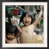 Filipino Children React as They Get a Shower Outside Their Homes Framed Photographic Print