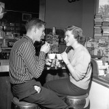 Teen Couple on Stools at Soda Fountain Drinking Shakes and Smiling at Each Other Photographic Print by H. Armstrong Roberts