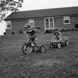 Boy and Girl Playing With Cycle and Pull Wagon Photographic Print by H. Armstrong Roberts