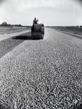 Highway Construction Worker Operating Heavy Machinery on Loose Gravel Road Photographic Print by H. Armstrong Roberts