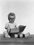 Baby Boy is Wearing Round Glasses While Reading a Very Large Book Photographic Print by H. Armstrong Roberts