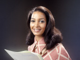 Smiling African-American Woman Reading From Papers Photographic Print by H. Armstrong Roberts