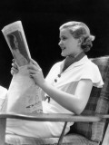 Smiling Blonde Woman Reading Newspaper While Sitting in Arm Chair Photographic Print by H. Armstrong Roberts