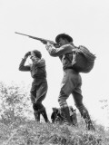 Couple in Brush, Man Aiming Hunting Rifle, Woman Standing Looking Through Binoculars Photographie par H. Armstrong Roberts