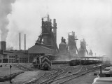 Industrial Site With Trains on Intersecting Tracks, Blast Furnaces in Background Photographic Print by H. Armstrong Roberts