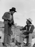 Two Cowboys at Campsite, One Standing, Pouring Coffee Photographie par H. Armstrong Roberts