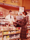 Woman at Pharmacy Counter Talking To Pharmacist Photographic Print by H. Armstrong Roberts