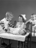 Boy and Girl Playing Doctor and Nurse Using Doll As a Patient Photographic Print by H. Armstrong Roberts