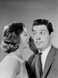 Woman Whispering Into Man's Ear, Man Pulling Funny Face Photographie par H. Armstrong Roberts