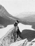 Two Cowboys on Top of Rocky Crag, One Man Kneeling, Aiming Hunting Rifle Photographie par H. Armstrong Roberts