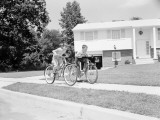 Boy and Girl Racing Along Suburban Street on Bicycles Photographic Print by H. Armstrong Roberts