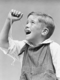 Boy Holding String Tied To Loose Front Tooth Photographic Print by H. Armstrong Roberts