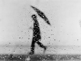 Silhouette of Man Carrying an Umbrella, Walking in the Rain Photographie par H. Armstrong Roberts