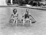 Couple Sitting on a Float in a Swimming Pool Photographic Print by H. Armstrong Roberts