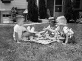 Three Small Children Playing on Front Lawn, Enjoying Picnic on Checkered Tablecloth Photographic Print by H. Armstrong Roberts