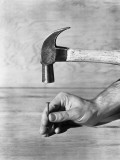 Man's Hand Holding Nail Down on Board With Other Hand Holding Hammer Photographic Print by H. Armstrong Roberts