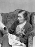 Woman in Striped Dress Sitting in Chair Reading Newspaper With Concerned Expression Photographic Print by H. Armstrong Roberts