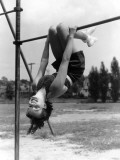 Smiling Teen Girl on Playground Hanging Upside Down on Monkey Bars Photographic Print by H. Armstrong Roberts