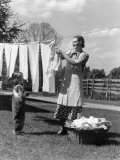 Mother and Daughter Doing Laundry, Hanging Wash on Clothesline in Backyard Fotografisk tryk af H. Armstrong Roberts