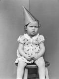 Girl Wearing Dunce Cap Sitting on Stool in Corner Photographic Print by H. Armstrong Roberts