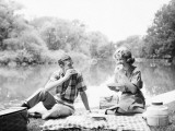 Couple Seated on Checkered Tablecloth With Picnic Basket and Cooler, Eating Sandwiches By Lake Photographic Print by H. Armstrong Roberts