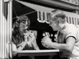 Teenage Couple Eating Hotdogs Outside at Refreshment Stand Table Photographic Print by H. Armstrong Roberts