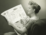 Woman Sitting in Armchair, Reading Newspaper, Smiling Photographic Print by George Marks