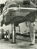 Man Repairing Uplifted Car, Low Section Photographic Print by George Marks