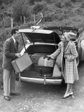 Couple Unloading Luggage From Trunk of Car Photographic Print by George Marks