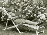 Woman Reading on Lounge Chair Outdoors Photographic Print by George Marks