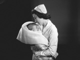 Nurse Hugging Newborn (0-3 Months) Wrapped in Blanket Photographic Print by George Marks