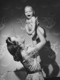 Woman Lifting Up Baby (6-9 Months) at Home Photographic Print by George Marks