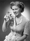 Woman Drinking Glass of Water With Look of Disgust Photographic Print by George Marks