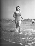 Woman in Swimsuit Running on Shoreline Photographic Print by George Marks