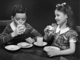 Brother and Sister Eating Sandwiches and Drinking Photographic Print by George Marks