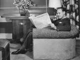 Man Sitting in Armchair, Reading Newspaper Photographic Print by George Marks