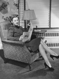 Woman Sitting in Armchair, Reading Newspaper Photographic Print by George Marks