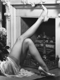 Woman Wearing Stockings Laying By Fireplace, Low Section Photographic Print by George Marks