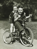 Two Young Boys (6-7) Riding Tricycle in Park, Portrait Lámina fotográfica por George Marks