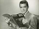 Elegant Young Man Reading Magazine in Studio Photographie par George Marks