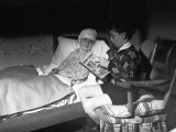 Boy (10-11) Reading To Friend Lying in Bed Photographic Print by George Marks