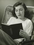 Woman Sitting on Armchair, Reading Book Photographic Print by George Marks