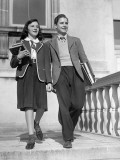 Teen Couple With Books Walking Outside School Photographic Print by George Marks