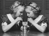 Twin Sisters Drinking Through Straws From Same Glass Photographic Print by George Marks